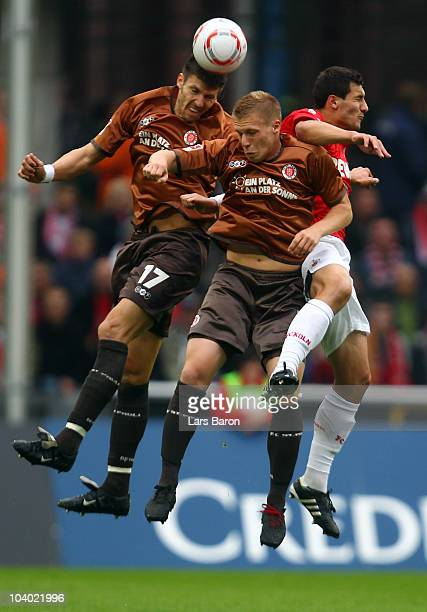 Fabian Boll and Rouwen Hennings of St Pauli go up for a header with Mato Jajalo of Koeln during the Bundesliga match between 1 FC Koeln and FC St...