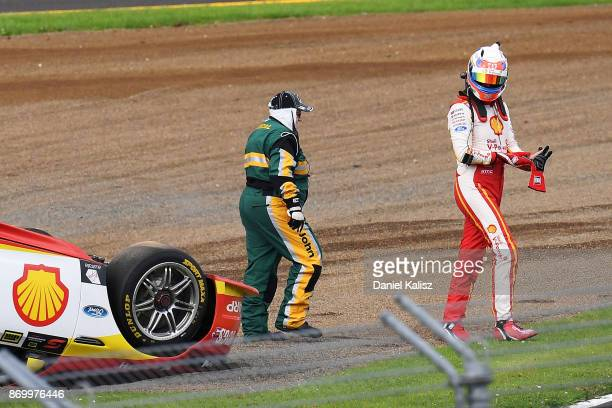 Fabian Coulthard driver of the Shell VPower Racing Team Ford Falcon FGX walks from his car after colliding with David Reynolds driver of the Erebus...