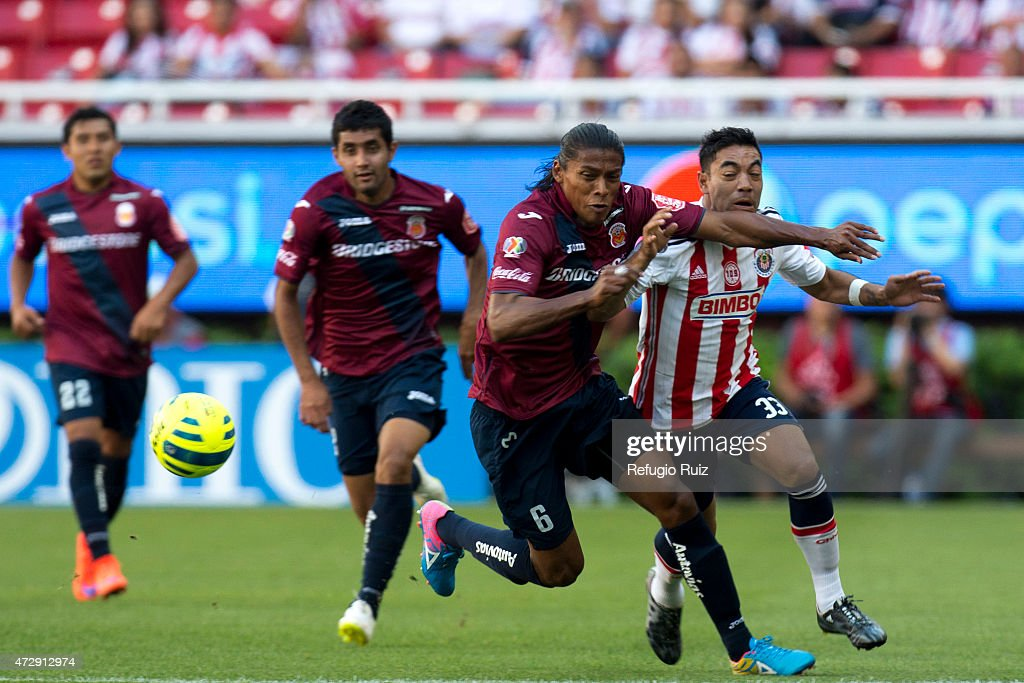 Fabian de la Mora of Chivas, fights for the ball with <a gi-track='captionPersonalityLinkClicked' href=/galleries/search?phrase=Joel+Huiqui&family=editorial&specificpeople=875917 ng-click='$event.stopPropagation()'>Joel Huiqui</a> of Morelia, during a match between Chivas and Morelia as part of 17th round of Clausura 2015 Liga MX at Omnilife Stadium on May10, 2015 in Zapopan, Mexico.