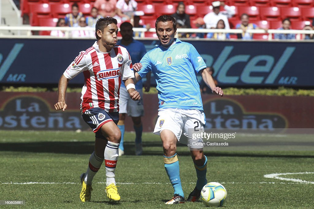 Fabian de la Mora of Chivas Guadalajara and <a gi-track='captionPersonalityLinkClicked' href=/galleries/search?phrase=Mario+Mendez&family=editorial&specificpeople=235993 ng-click='$event.stopPropagation()'>Mario Mendez</a> of San Luis fight for the ball during a match of the Clausura Liga MX Round 5 in Omnilife Stadium on February 3, 2013 in Guadalajara, Mexico.