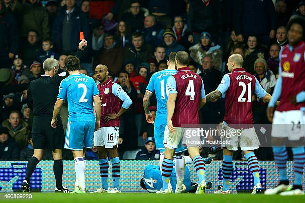 Fabian Delph of Aston Villa receives a red card from referee Martin Atkinson during the Barclays Premier League match between Aston Villa and...