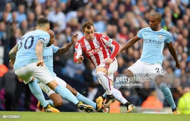 Fabian Delph of Manchester City and Fernandinho of Manchester City tackle Xherdan Shaqiri of Stoke City during the Premier League match between...