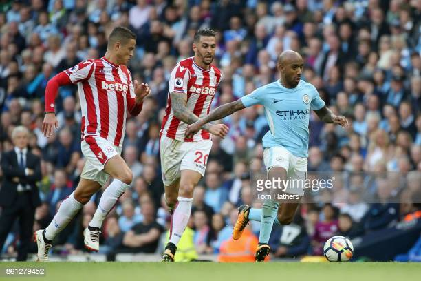 Fabian Delph of Manchester City is put under pressure from Geoff Cameron of Stoke City during the Premier League match between Manchester City and...