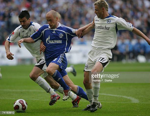 Fabian Ernst of Schalke is tackled by Radim Kucera and Petr Gabriel of Bielefeld during the Bundesliga match between FC Schalke 04 and Arminia...