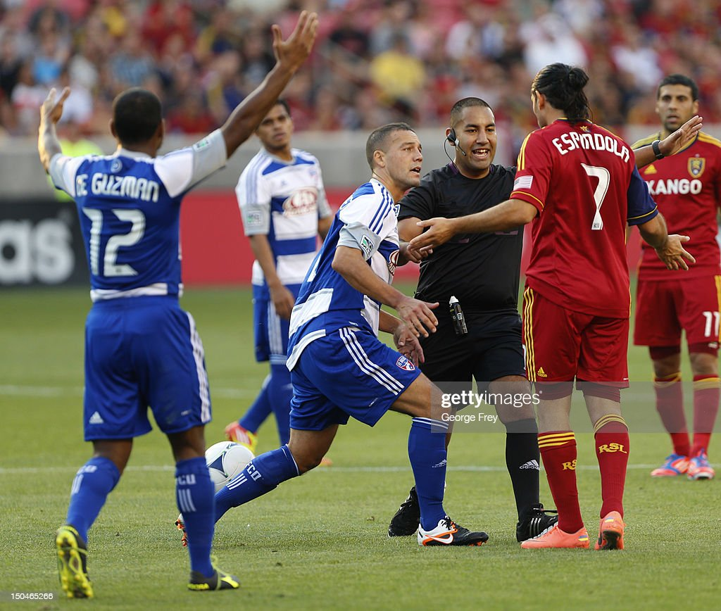 <a gi-track='captionPersonalityLinkClicked' href=/galleries/search?phrase=Fabian+Espindola&family=editorial&specificpeople=4476356 ng-click='$event.stopPropagation()'>Fabian Espindola</a> #7 of Real Salt Lake and <a gi-track='captionPersonalityLinkClicked' href=/galleries/search?phrase=Daniel+Hernandez&family=editorial&specificpeople=2157363 ng-click='$event.stopPropagation()'>Daniel Hernandez</a> #2 of FC Dallas are held back by official Juan Guzan as Julian De Guzman #12 reacts during the first half of an MLS soccer game August 18, 2012 at Rio Tinto Stadium in Sandy, Utah. FC Dallas beat Real Salt Lake 2-1.