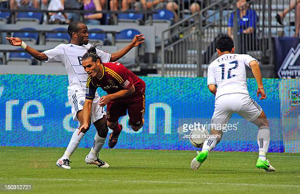 Fabian Espindola of Real Salt Lake gets tripped up by Dane Richards of the Vancouver Whitecaps while his teammate Lee YoungPyo looks on at BC Place...