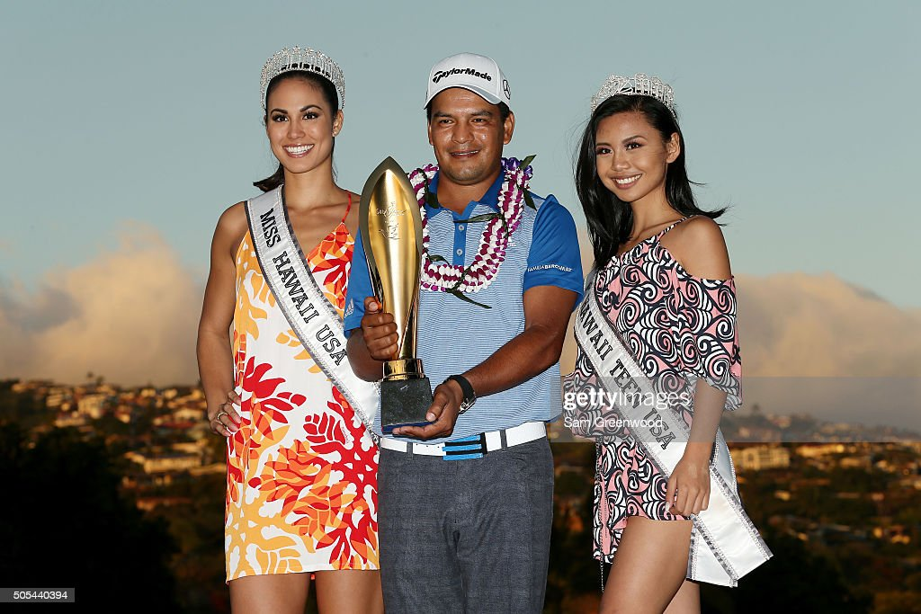 Fabian Gomez of Argentina celebrates with the winner's trophy Miss Hawaii USA and Miss Hawaii Teen USA after defeating Brandt Snedeker during a...