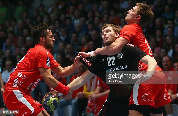 Fabian Gutbrod of Germany is challenged by Michael Allendorf and Christian Hildebrand of Melsungen during a benefit match between the German national...