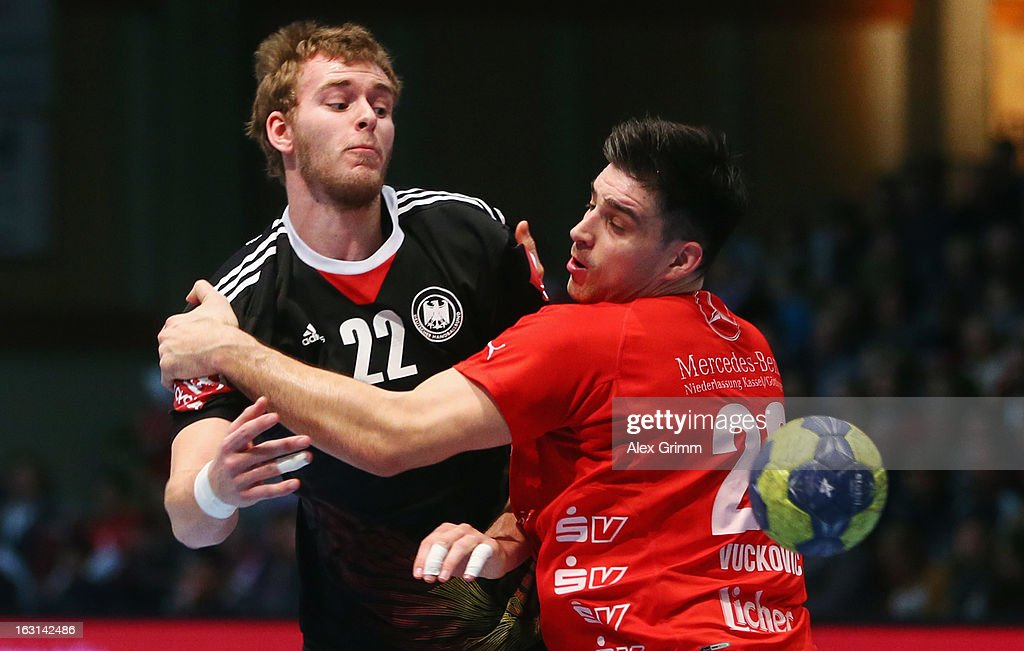 Fabian Gutbrod (L) of Germany is challenged by Nenad Vuckovic of Melsungen during a benefit match between the German national handball team and MT Melsungen at Rothenbach-Halle on March 5, 2013 in Kassel, Germany.