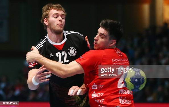 Fabian Gutbrod of Germany is challenged by Nenad Vuckovic of Melsungen during a benefit match between the German national handball team and MT...
