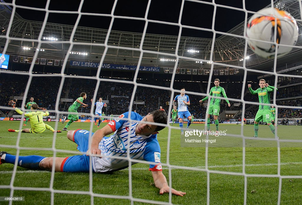 <a gi-track='captionPersonalityLinkClicked' href=/galleries/search?phrase=Fabian+Johnson&family=editorial&specificpeople=677415 ng-click='$event.stopPropagation()'>Fabian Johnson</a> of Gladbach scores his team's third goal past goalkeeper <a gi-track='captionPersonalityLinkClicked' href=/galleries/search?phrase=Oliver+Baumann&family=editorial&specificpeople=4645207 ng-click='$event.stopPropagation()'>Oliver Baumann</a> of Hoffenheim and Fabian Schaer of Hoffenheim during the Bundesliga match between 1899 Hoffenheim and Borussia Moenchengladbach at Wirsol Rhein-Neckar-Arena on November 28, 2015 in Sinsheim, Germany.