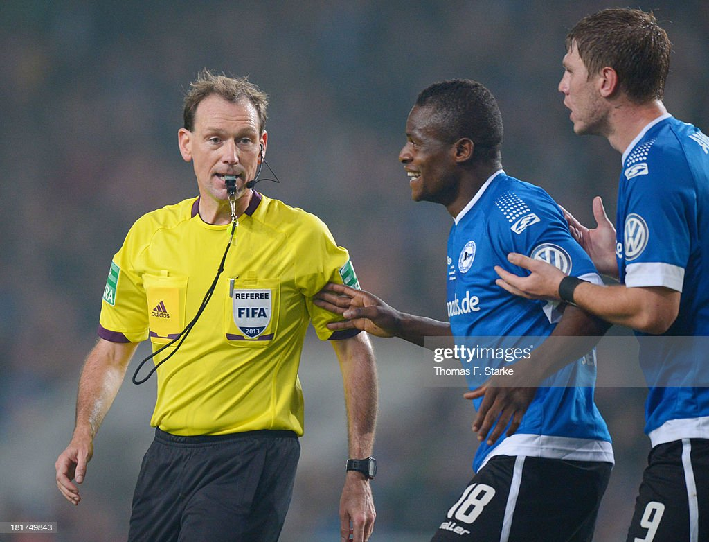 Fabian Klos (R) and Francky Sembolo (C) of Bielefeld argue with referee Florian Meyer during the DFB Cup match between Arminia Bielefeld and Bayer 04 Leverkusen at Schueco Arena on September 24, 2013 in Bielefeld, Germany.