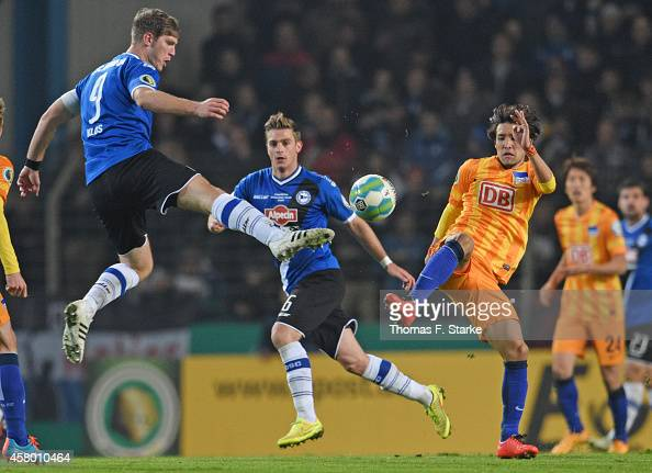Fabian Klos of Bielefeld and Hajime Hosogai of Berlin fight for the ball during the DFB Cup match between Arminia Bielefeld and Hertha BSC at Schueco...