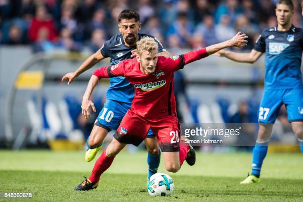 Fabian Lustenberger of Berlin is challenged by Kerem Demirbay of Hoffenheim during the Bundesliga match between TSG 1899 Hoffenheim and Hertha BSC at...