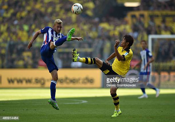 Fabian Lustenberger of Hertha BSC and Shinji Kagawa of Borussia Dortmund vie for the ball during the Bundesliga match between Borussia Dortmund and...