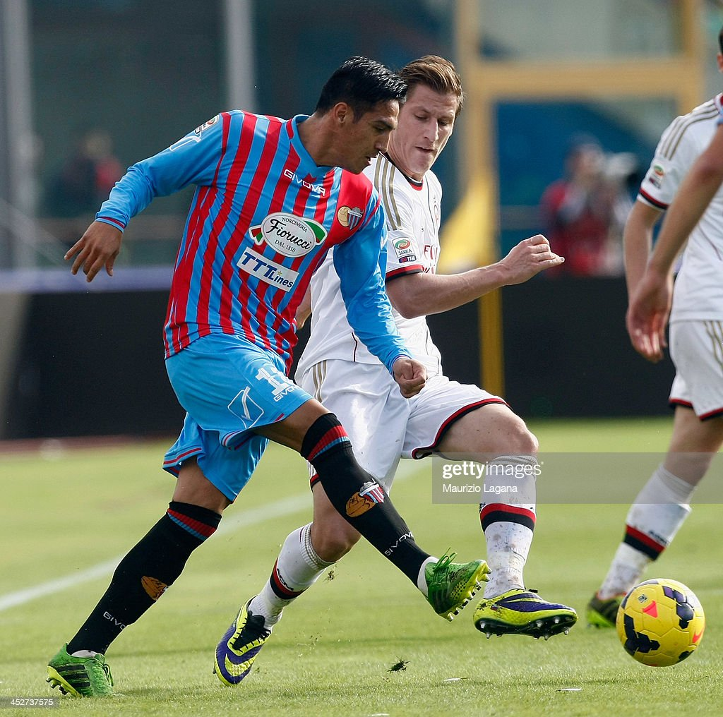 Fabian Monzon (L) of Catania competes for the ball with Valter Birsa of Milan during the Serie A match between Calcio Catania and AC Milan at Stadio Angelo Massimino on December 1, 2013 in Catania, Italy.