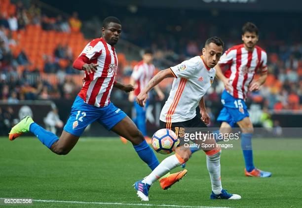 Fabian Orellana of Valencia competes for the ball with Elderson Uwa Echiejile of Real Sporting de Gijon during the La Liga match between Valencia CF...