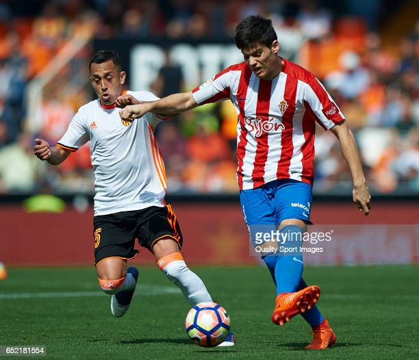 Fabian Orellana of Valencia competes for the ball with Jorge Mere of Real Sporting de Gijon during the La Liga match between Valencia CF and Real...
