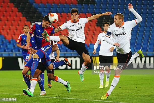 Fabian Schaer of Basel is challenged by Eduardo Vegas and Jeremy Mathieu of Valencia during the UEFA Europa League Quarter Final first leg match...