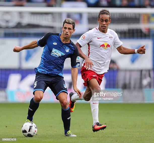 Fabian Schaer of Hoffenheim is challenged by Yussuf Poulsen of Leipzig during the Bundesliga match between TSG 1899 Hoffenheim and RB Leipzig at...