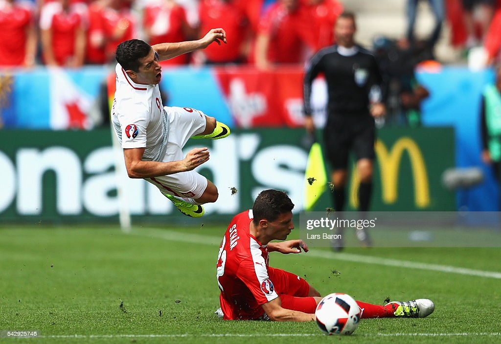 Fabian Schaer of Switzerland fouls <a gi-track='captionPersonalityLinkClicked' href=/galleries/search?phrase=Robert+Lewandowski&family=editorial&specificpeople=5532633 ng-click='$event.stopPropagation()'>Robert Lewandowski</a> of Poland resulting in an yellow card during the UEFA EURO 2016 round of 16 match between Switzerland and Poland at Stade Geoffroy-Guichard on June 25, 2016 in Saint-Etienne, France.