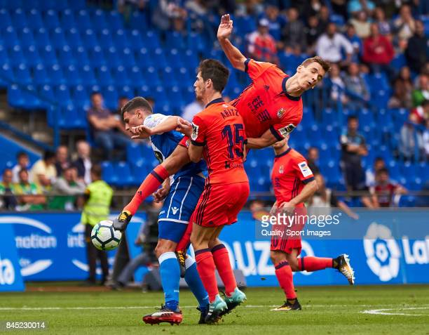 Fabian Schar of Deportivo de La Coruna competes for the ball with Aritz Elustondo of Real Sociedad and Diego Llorente Rios of Real Sociedad during...