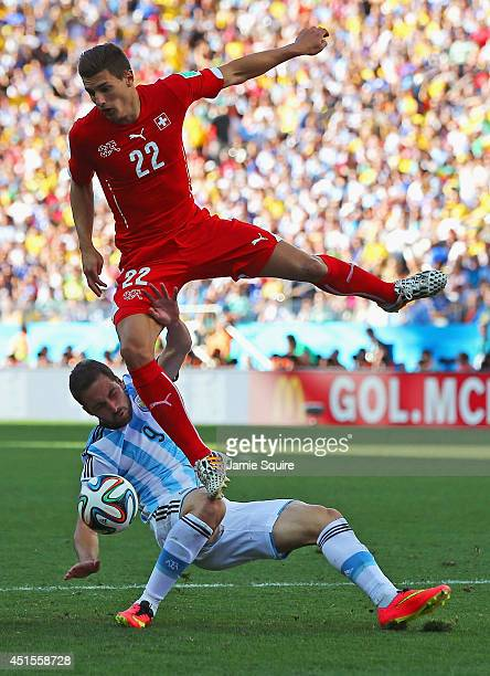 Fabian Schar of Switzerland collides with Gonzalo Higuain of Argentina during the 2014 FIFA World Cup Brazil Round of 16 match between Argentina and...