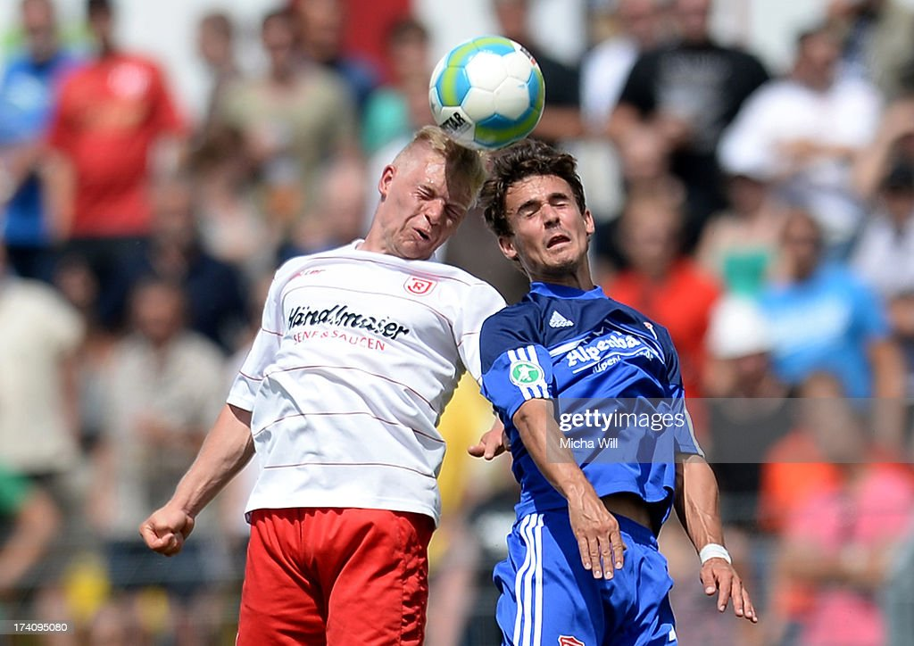 Fabian Trettenbach (L) of Regensburg and Dominik Rohracker of Unterhaching jump for a header during the Third League match between Jahn Regensburg and SpVgg Unterhaching at Jahnstadion on July 20, 2013 in Regensburg, Germany.