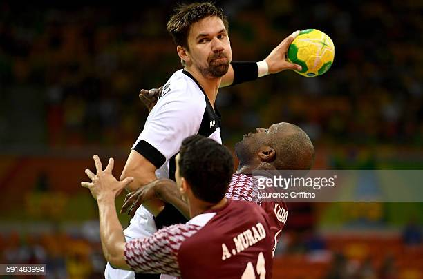 Fabian Wiede of Germany gets under pressure of Abdulrazzaq Murad and Hassan Mabrouk of Qatar during the Men's Quarterfinal Handball contest between...