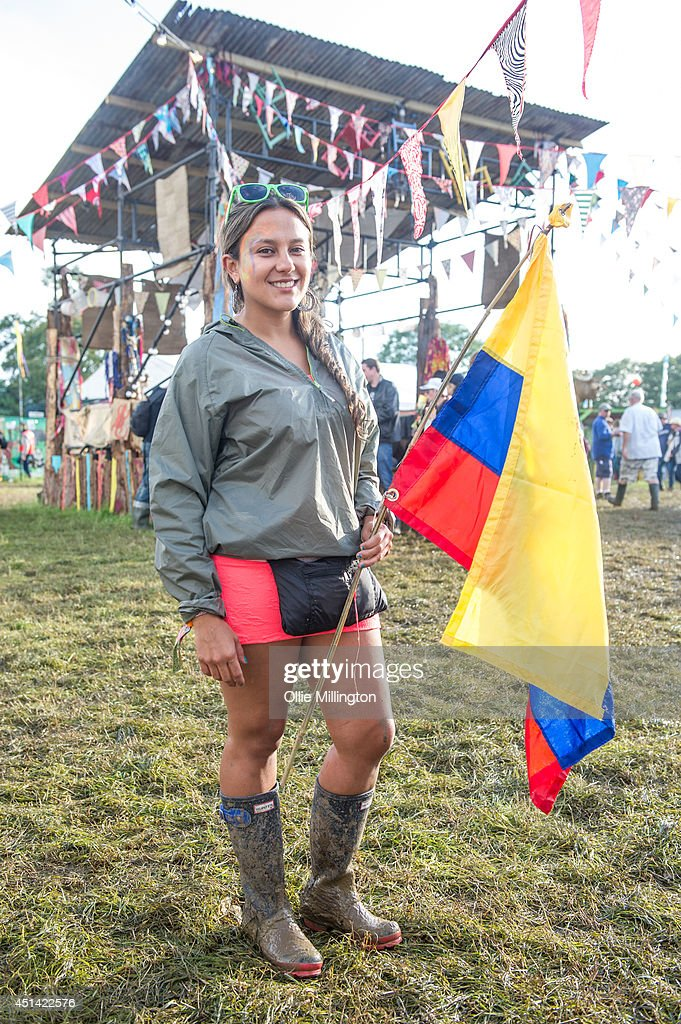 Fabiana ,22 ,a muscian from Bogota, Columbia attends the Glastonbury Festival on day 2 wearing a Topshop dress, a TopShop coat and Hunter wellies at Worthy Farm on June 28, 2014 in Glastonbury, England.