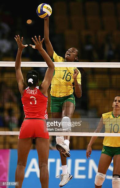 Fabiana Claudino of Brazil spikes the ball against Nancy Carrillo de la Paz of Cuba in the women's indoor Volleyball bronze medal match on August 28...