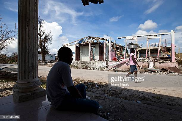 Fabien Museau peers out from the porch of a home on October 11 at the damage caused by Hurricane Matthew in Port Salut Haiti