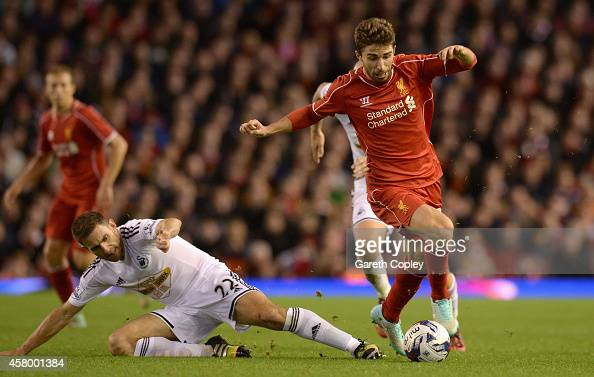 Fabio Borini of Liverpool is tackled by Angel Rangel of Swansea during the Capital One Cup Fourth Round match between Liverpool and Swansea City at...