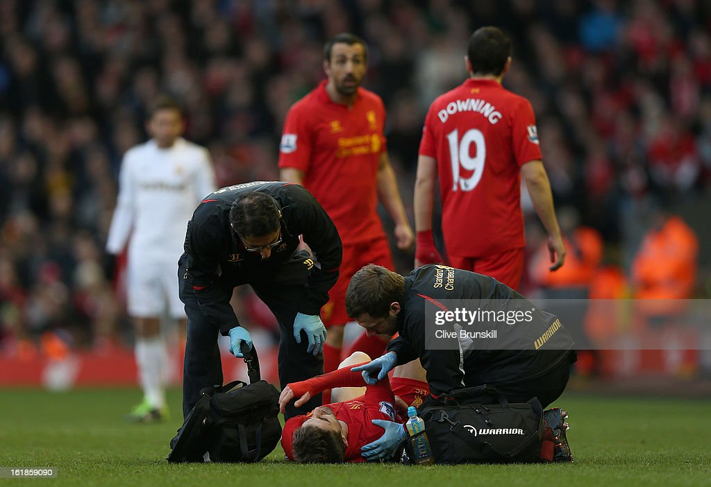 Fabio Borini of Liverpool is treated by medical staff as he lies injured after dislocating his shoulder during the Barclays Premier League match between Liverpool and Swansea City at Anfield on February 17, 2013 in Liverpool, England.