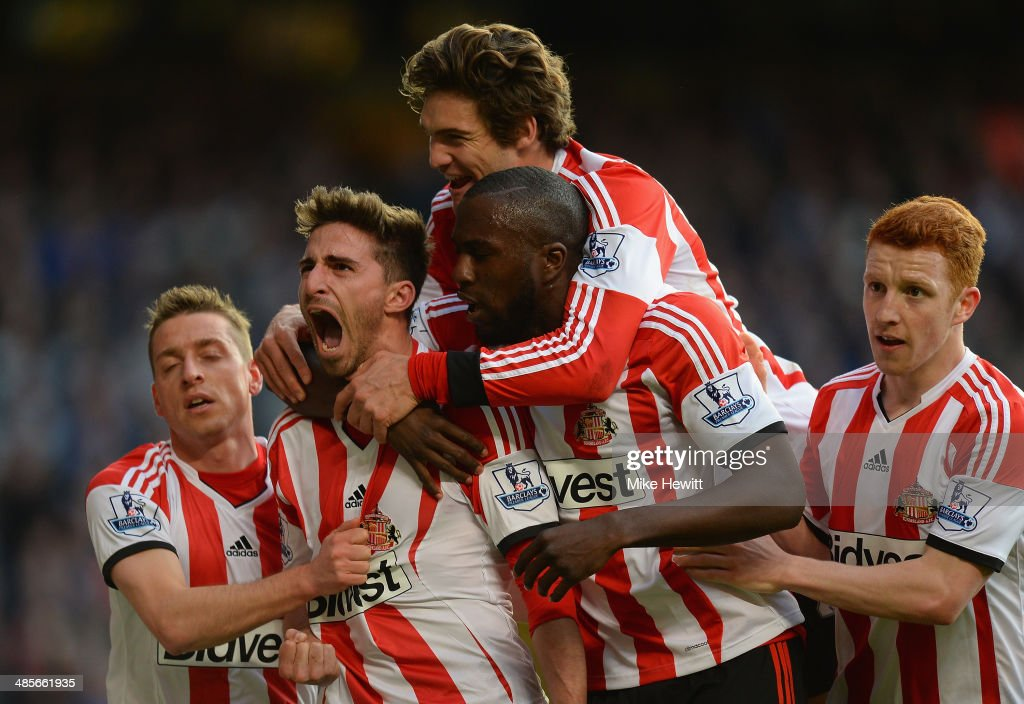 Fabio Borini of Sunderland is mobbed by team mates after scoring the winner from the penalty spot during the Barclays Premier League match between Chelsea and Sunderland at Stamford Bridge on April 19, 2014 in London, England.
