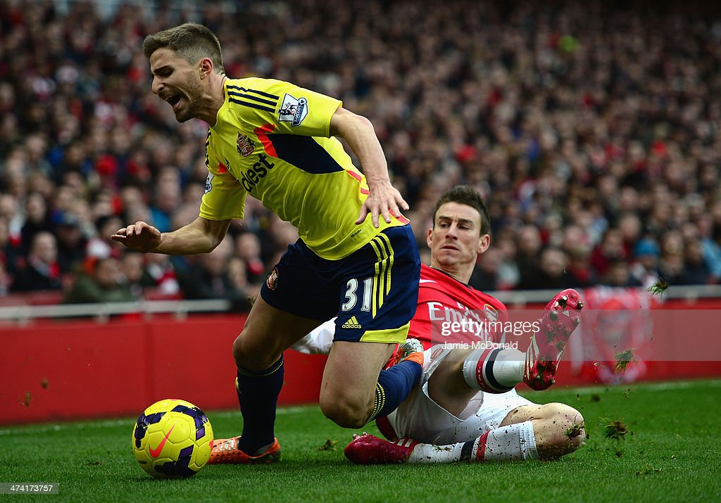 Fabio Borini of Sunderland is tackled by Laurent Koscielny of Arsenal during the Barclays Premier League match between Arsenal and Sunderland at Emirates Stadium on February 22, 2014 in London, England.