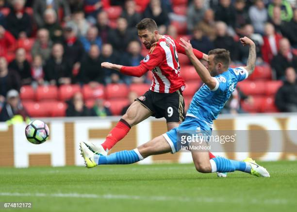 Fabio Borini of Sunderland shoots on goal under pressure from Steve Cook of AFC Bournemouth during the Premier League match between Sunderland and...