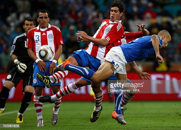 Fabio Cannavaro of Italy is tackled by Cristian Riveros of Paraguay during the 2010 FIFA World Cup South Africa Group F match between Italy and...