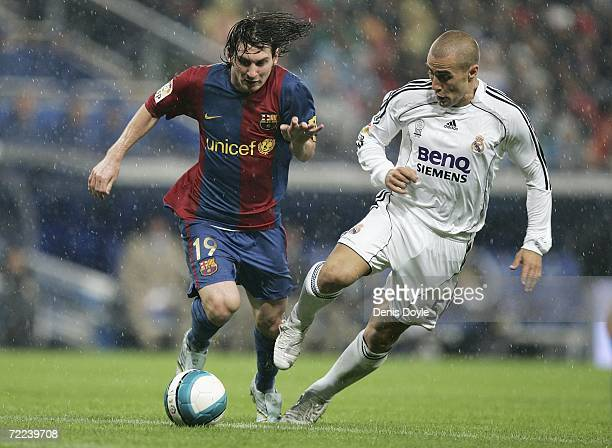 Fabio Cannavaro of Real Madrid tackles Lionel Messi of Barcelona during the Primera Liga match between Real Madrid and Barcelona at the Santiago...