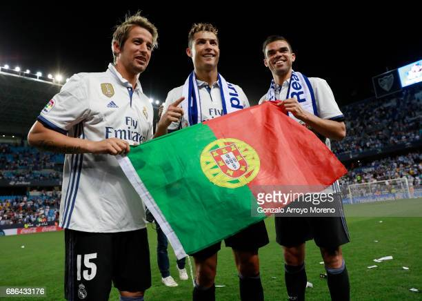 Fabio Coentrao Cristiano Ronaldo and Pepe of Real Madrid celebrate after they are crowned champions following the La Liga match between Malaga and...