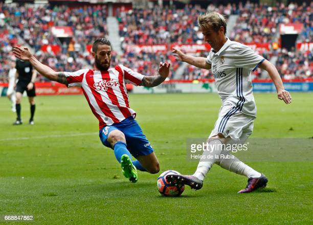 Fabio Coentrao of Real Madrid and Lillo of Real Sporting de Gijon compete for the ball during the La Liga match between Real Sporting de Gijon and...