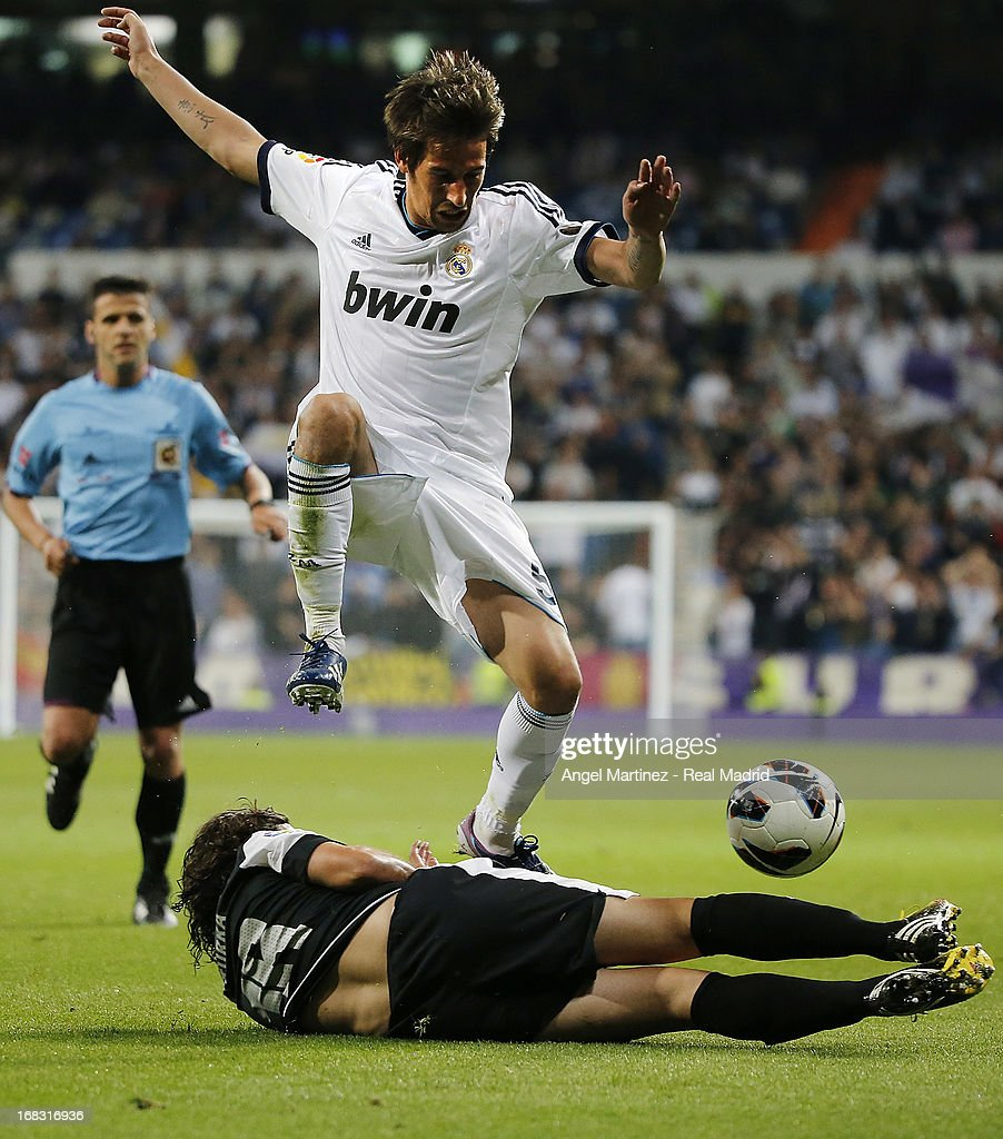 Fabio Coentrao of Real Madrid competes for the ball with Manuel Iturra of Malaga during the La Liga match between Real Madrid and Malaga at Estadio Santiago Bernabeu on May 8, 2013 in Madrid, Spain.