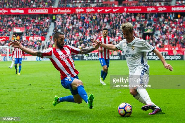 Fabio Coentrao of Real Madrid duels for the ball with Manuel Castellano 'Lillo' of Real Sporting de Gijon during the La Liga match between Real...