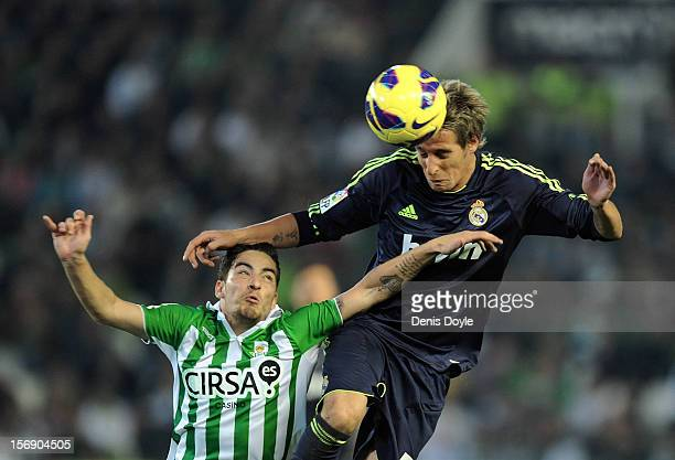 Fabio Coentrao of Real Madrid goes for a high ball against Salvador Arga of Real Betis Balompie during the La Liga match between Real Betis Balompie...