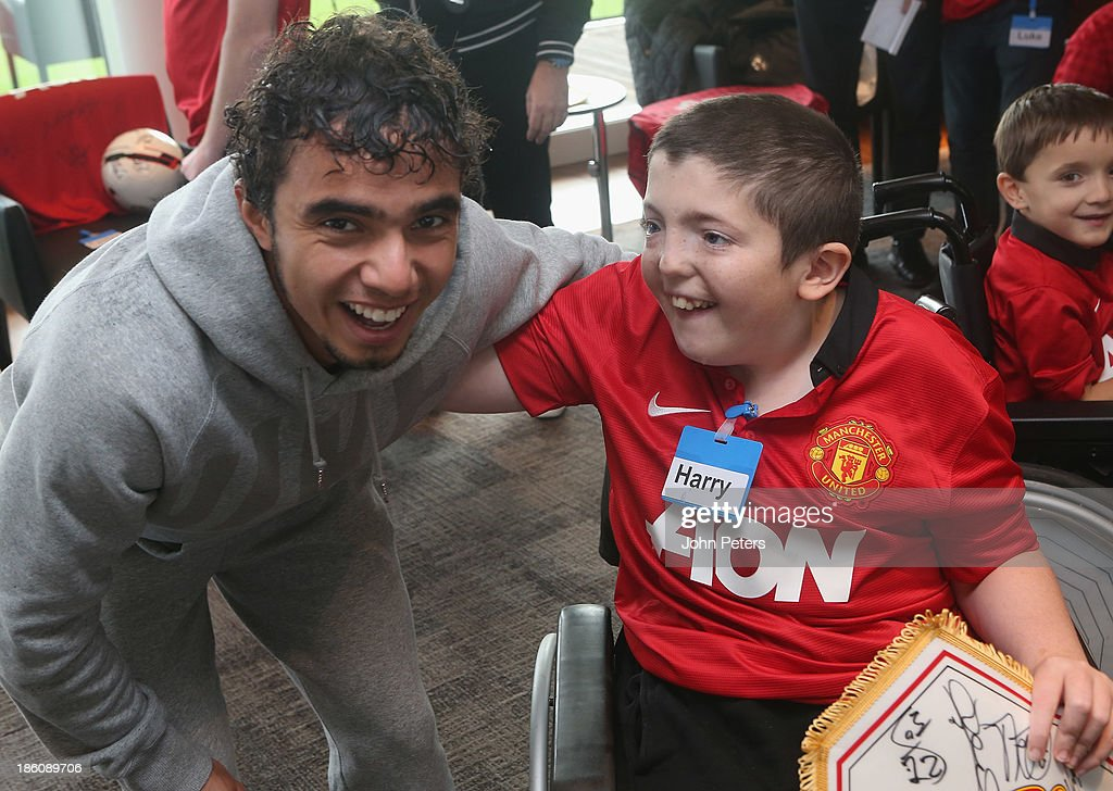 Fabio da Silva of Manchester United meets Harry during a Manchester United Foundation Dream Day, for fans with life-limiting illnesses, at Aon Training Complex on October 28, 2013 in Manchester, England.