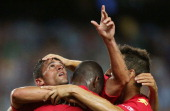 Fabio Ferreira of Adelaide celebrates scoring a goal with team mates Bruce Djite and Isaias Sanchez during the round 18 ALeague match between Sydney...