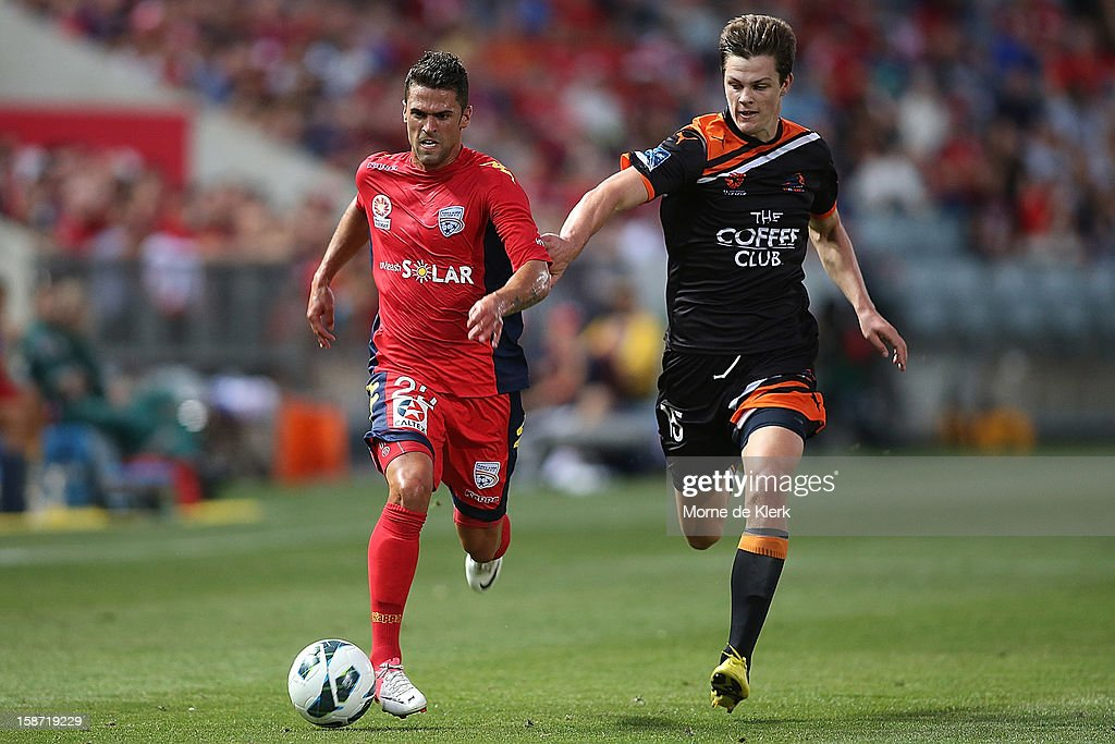 Fabio Ferreira of Adelaide gets away from James Donachie of Brisbane during the round 13 A-League match between Adelaide United and the Brisbane Roar at Hindmarsh Stadium on December 26, 2012 in Adelaide, Australia.