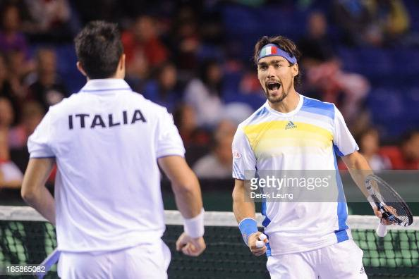Fabio Fognini of Italy celebrates with teammate Daniele Bracciali after winning a set during his doubles match against Vasek Pospisil and Daniel...