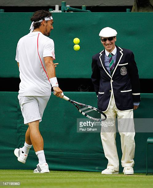 Fabio Fognini of Italy entertains a line judge by bouncing two balls during his Gentlemen's Singles second round match against Roger Federer of...