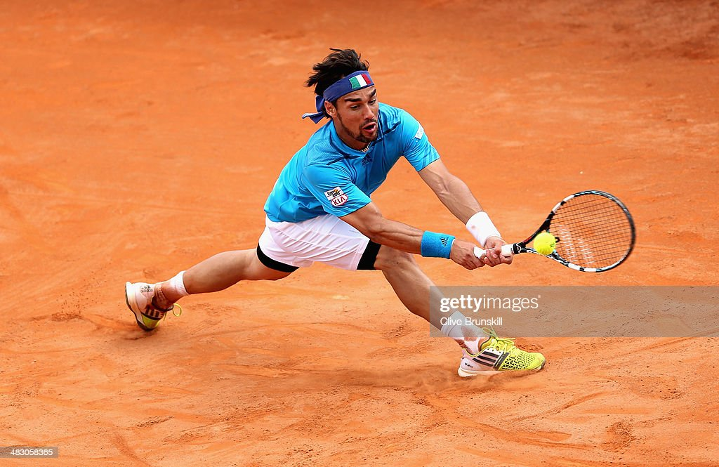Fabio Fognini of Italy slides to play a backhand during his straight sets victory against Andy Murray of Great Britain during day three of the Davis Cup World Group Quarter Final match between Italy and Great Britain at Tennis Club Napoli on April 6, 2014 in Naples, Italy.